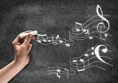 Businessman hand with chalk draws music notes sketch on chalkboard. Freehand white chalk illustration on blackboard. Music art school advertisement. Musician or composer writing music notes. Фото со стока