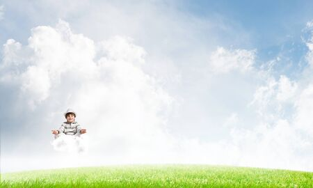 Young little boy keeping eyes closed and looking concentrated while meditating on cloud 版權商用圖片