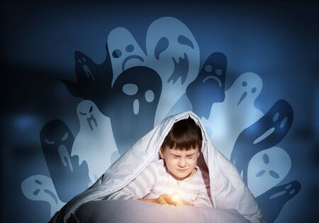 Scared boy hiding under blanket from imaginary spooky monsters.