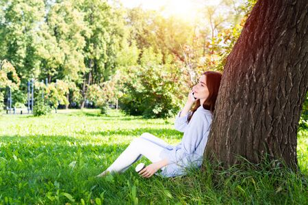 Young redhead woman talking on smartphone under tree in park on sunny day.