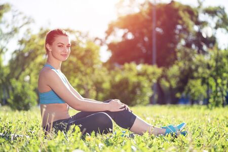 Beautiful smiling girl in active wear relax in park at sunrise.