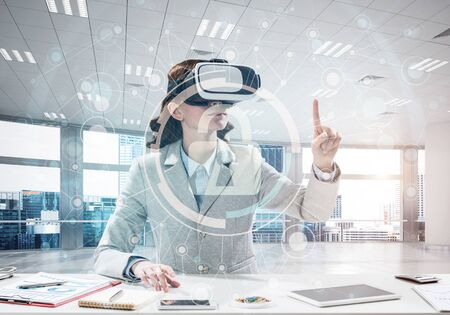 Horizontal shot of confident young business woman in suit using virtual reality headset Stock Photo