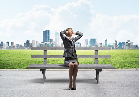 Stressful woman sitting on wooden bench.