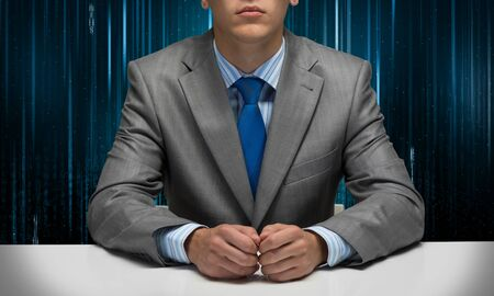 Man with folded hands sitting at desk.