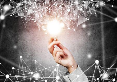 어두운 벽 배경에 빛나는 램프와 추상 디지털 네트워크 연결을 가진 여자 손. 과학 연구 및 혁신 회사. 글로벌 네트워크 기술과 성공적인 비즈니스 솔루션.