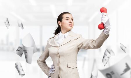 Woman keep at distance vintage red phone. Elegant operator in white business suit posing with landline phone in office with flying paper documents. Hotline telemarketing and business communication. 版權商用圖片