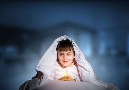 Happy child with flashlight hiding under blanket. Smiling kid lying in bed at home. Funny game at bedtime. Young boy can not sleep at night. Cheerful boy in pajamas on deep blue blurred background.