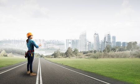Woman in safety helmet standing on asphalt highway with blueprint. Back view architect in workwear checking construction on cityscape background. Road infrastructure reconstruction and development