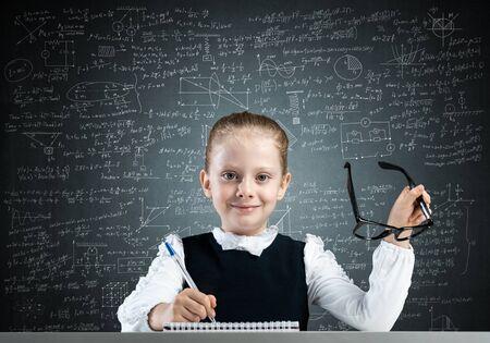 Glimlachend meisje in schoolkleding die haar huiswerk doet. Tijd om concept te bestuderen. Gelukkig schoolmeisje met een bril die aan het bureau zit en in een notitieboekje schrijft. Onderzoek en onderwijs op de basisschool. Stockfoto