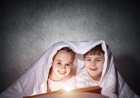 Smiling kids reading magic fairy tales in bed. Happy children with flashlight hiding under blanket. Little friends having fun at bedtime. Young boy and girl in pajamas spend time together in bedroom.