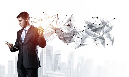 Handsome manager pointing on abstract network composition. Man in business suit on white background. Mixed media with virtual network. Professional business assistance, financial maintenance support