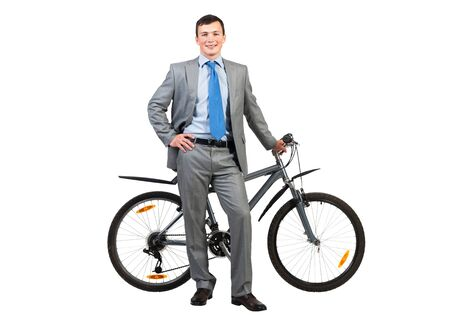 Smiling man in grey business suit and tie standing near bike. Cheerful businessman with bicycle. Male cyclist with hand on waist isolated on white background. Healthy leisure and activity
