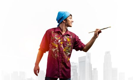Young male artist holding paintbrush. Happy painter in dirty shirt and bandana standing on background modern city. Creative hobby and artistic occupation concept with copy space Stockfoto