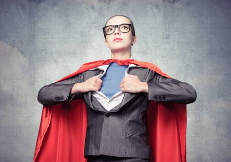 Beautiful business woman opening her shirt like a superhero. Confident lady in glasses with red cape. Brave super woman ready for new wins. Woman wears superhero t-shirt under her business suit.