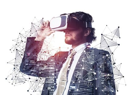 Businessman wearing VR goggles and exploring virtual reality. Man standing and touching VR headset. Studio photo businessperson in formal wear against white background. Cyber technology in business