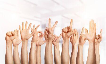 Reihe von Mannhänden, die verschiedene Gesten zeigen. Ok, mit dem Finger zeigen, Sieg, Finger spreizen, Faust geballt und Daumen hoch. Menschliche Hände, die auf hellem verschwommenem Hintergrund gestikulieren. Viele Arme zusammen erhoben.