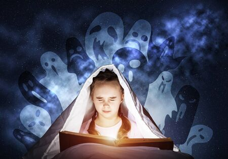 Scared kid with reading book under blanket. Afraid girl with closed eyes lying in bed at home. Child reading scary stories. Girl in pajamas and imaginary ghosts. Bright light shining from open book.