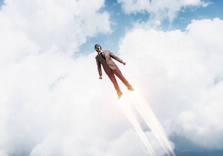 Businessman in aviator hat flying in cloudy blue sky as superhero. Business person  with jet flame flying planet atmosphere. Goal achievement concept. Career ambition and growth.