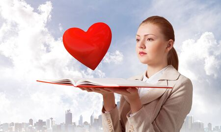 Beautiful woman looks at red heart above opened notebook. Elegant girl in white business suit with open book on background of cityscape and cloudy blue sky. Love and tenderness concept.