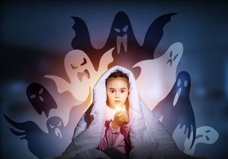 Scared girl with flashlight hiding under blanket from imaginary phantoms. Frightened kid sitting in bed on night sky background. Girl in pajamas and boo ghosts silhouettes
