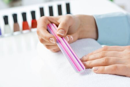 Woman using nail file and create perfect nails shape. Grinding female nails with nail file tool and preparing for apply nail polish. Woman doing herself nail care procedure at home. Beauty and hygiene 写真素材 - 133564387