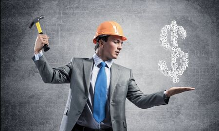 Businessman going to crash with hammer dollar symbol. Young handsome man in business suit and safety helmet standing on grey wall background. Financial crisis, bankruptcy and inflation pressure.
