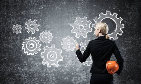 Businesswoman draws cogwheel mechanism on chalkboard. Woman in business suit with safety helmet. Mechanical system engineering and project management. Business solution planning and designing.