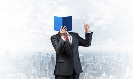 Businessman covered his face with organizer and finger pointing up. Man in business suit and tie standing on cityscape background. Education and professional knowledges. Direction and instruction. Imagens