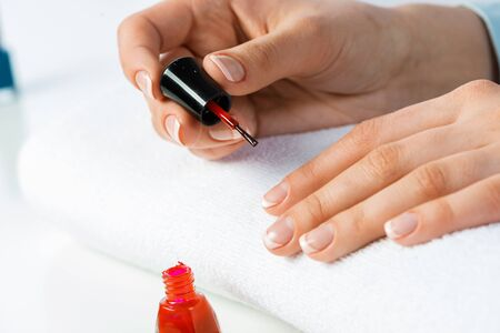 Woman giving herself elegant manicure at home. Closeup of beautiful female hand applying red nail polish at white table. Professional nail care and beautician procedure. Stylish nail art concept 写真素材 - 133582658