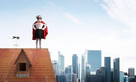Junges Mädchen im Superheldenkostüm, das auf dem Ziegeldach des Hauses steht. Gemischte Medien Standard-Bild
