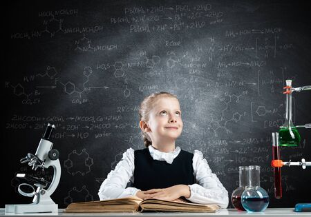 Schoolgirl sitting at desk with open book. Happy girl scientist studying in classroom with chalkboard. Chemical laboratory with glass flasks and test tubes. Clever girl in schoolwear reading book on