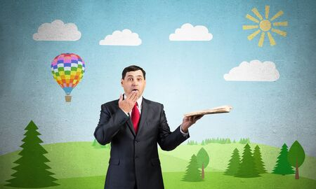 Surprised businessman holding open old book. Startled adult man in business suit and tie standing on background of nature landscape with greenfield illustration. Education and knowledges.
