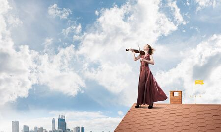 Young attractive girl playing violin at top oo brick roof. Mixed media Banque d'images