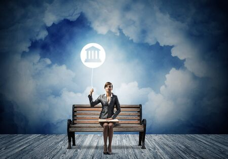 Young woman with open book on wooden bench outdoor. Legal assistance and representation. Beautiful girl with court of justice or bank symbol in night sky. Skyscape with deep blue night sky.
