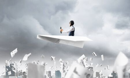 Crisis management and control in difficult situation concept. Businessman in aviator hat driving paper plane in storm. Pilot flying in small airplane. Megalopolis panorama with dramatic sky. 版權商用圖片