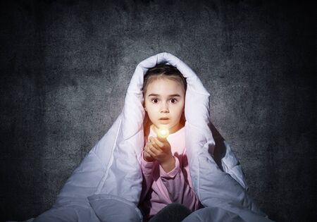 Frightened girl with flashlight hiding under blanket. Scared kid lying in his bed at home. Night terrors of child. Little girl can not sleep at night. Child in pajamas on background of grey wall.