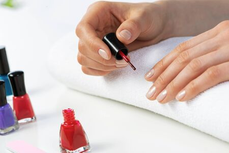 Woman giving herself elegant manicure at home. Closeup of beautiful female hand applying red nail polish at white table. Professional nail care and beautician procedure. Stylish nail art concept 写真素材 - 133627925