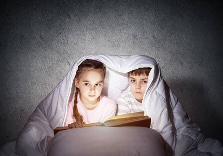 Little girl and boy looking at each other under blanket. Children reading magic stories in bed before going to sleep. Young sister and brother in pajamas together on background of grey wall.