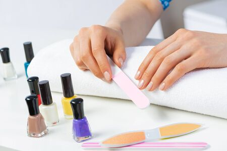 Woman using nail file and create perfect nails shape. Colorful nail polish bottles on table. Grinding female nails with nail file. Woman doing herself nail care procedure at home. Beauty and hygiene 写真素材 - 133653265