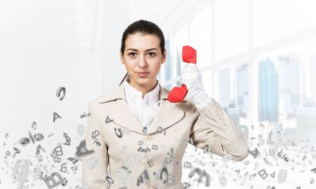 Attractive woman holding vintage red phone in office with flying various letters. Elegant operator in white business suit posing with landline phone. Hotline telemarketing and business communication. Stock Photo