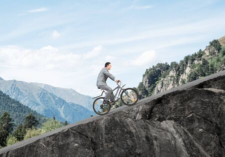 Businessman riding uphill by bike. Nature landscape with copy space. Man in business suit riding bicycle on mountain road. Cyclist on background of blue sky. Healthy lifestyle and outdoor activity Archivio Fotografico