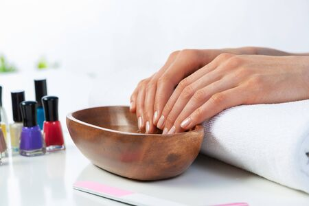 Woman hands in wooden bowl with water. Spa procedure and relaxation. Female hands preparing for manicure. Professional nail care and beautician service. Beauty and healthy lifestyle. 写真素材 - 133653415