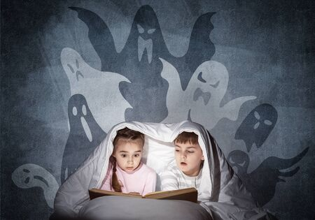 Engrossed little kids reading book in bed. Brother and sister together hiding under blanket. Fearful children in pajamas and imaginary monsters on background of grey wall. Child reading fairy tales.