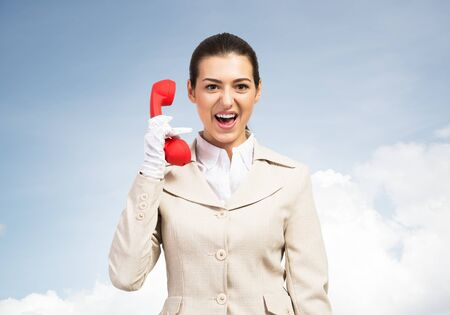 Expressive woman shouting into red handset phone. Operator in business suit standing with cellphone on blue sky background. Business assistance and consultation. Customer service support concept Banco de Imagens