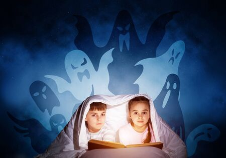 Cute girl and boy reading kids book in bed. Children with flashlight lying under blanket together. Kids in pajamas and funny ghosts silhouettes back on night sky. Children reading magic fairy tales