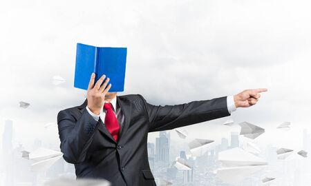 Businessman covered his face with organizer and finger pointing side. Man in business suit and tie standing on cityscape background with flying paper planes. Education and professional knowledges. Imagens