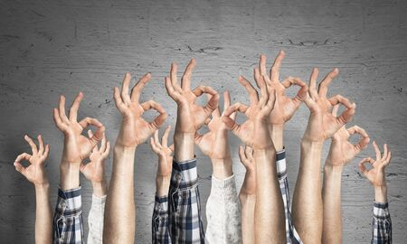 Row of man hands showing okay gesture. Agreement and approval group of signs. Human hands gesturing on background of grey wall. Many arms raised together and present popular gesture.
