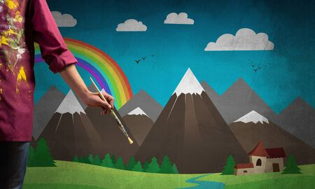 Close up artist hand holding paintbrush. Painter in shirt standing on background colorful picture. Summer landscape with mountains, blue sky and rainbow artwork. Creative hobby and profession. Banco de Imagens - 133772634