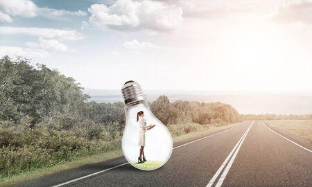 Young businesswoman trapped inside of light bulb on asphalt road Reklamní fotografie
