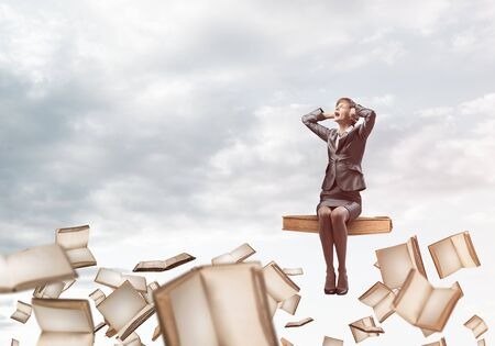 Stressful woman sitting on big book and flying in blue sky. Screaming girl in business suit keeps hands on head. Nervous businesswoman in despair on background of cloudscape with open books.